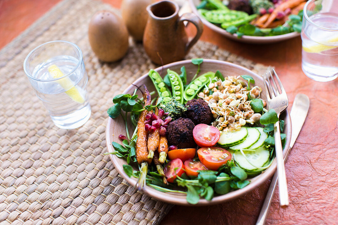 Salad bowl with cucumber, falafel, pomegranate, roast carrots, snap peas, tomato and watercress