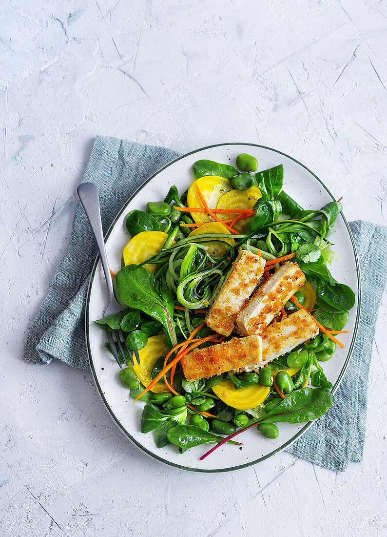 Vegan salad with yellow beet, zucchini, beans and breaded tofu