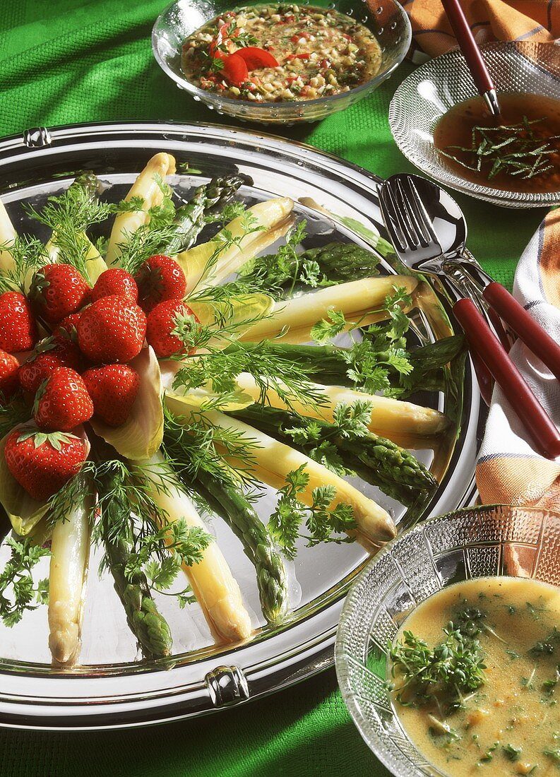 Asparagus platter with three kinds of sauce, garnished with strawberries