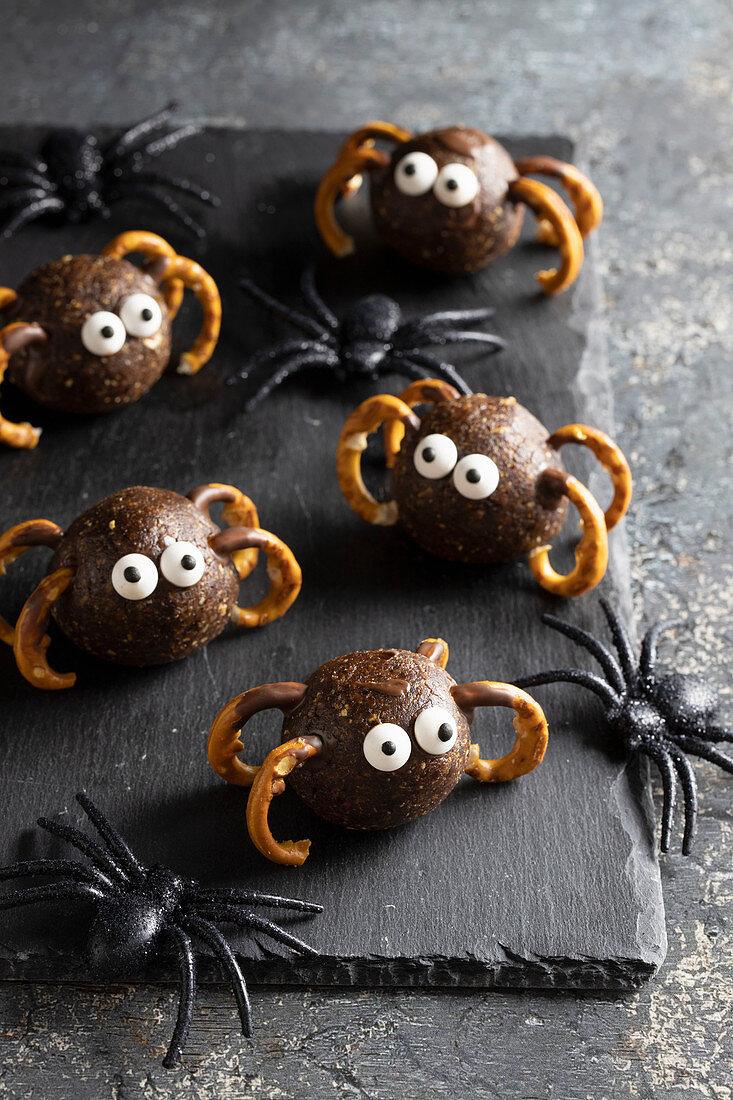 Halloween spider truffles from dates, peanut butter and granola, leggs from precels, sugar eyes