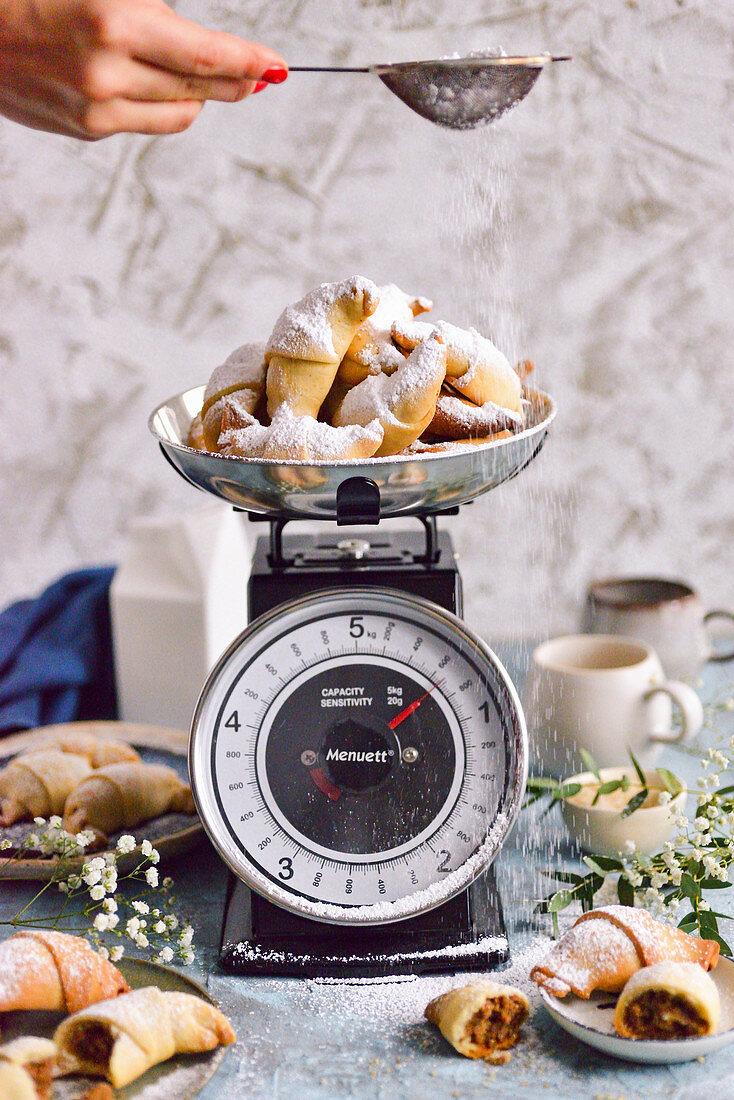 Brittle croissants in powdered sugar on a kitchen scale