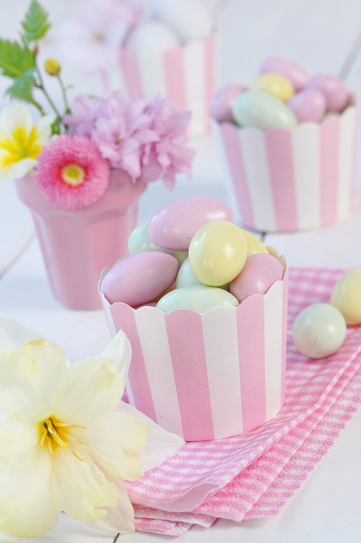 Sugar eggs in paper cupcake holders next to narcissus flower