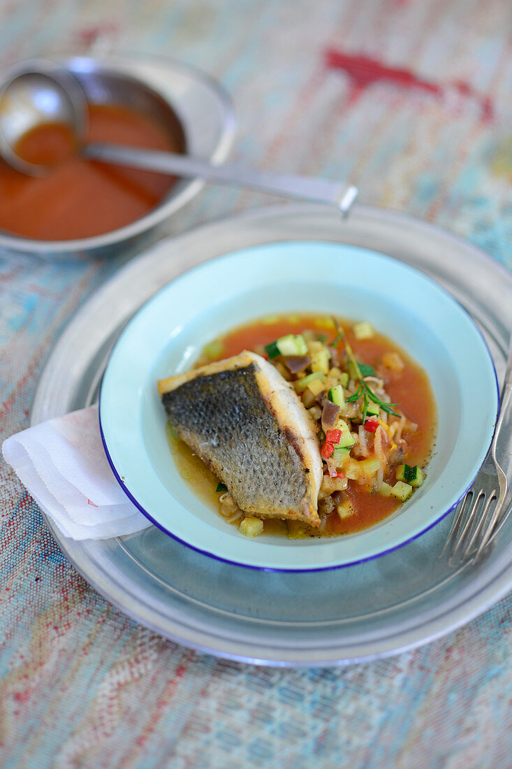 Loup de mer on a vegetable ragout with tomato and mace sugo