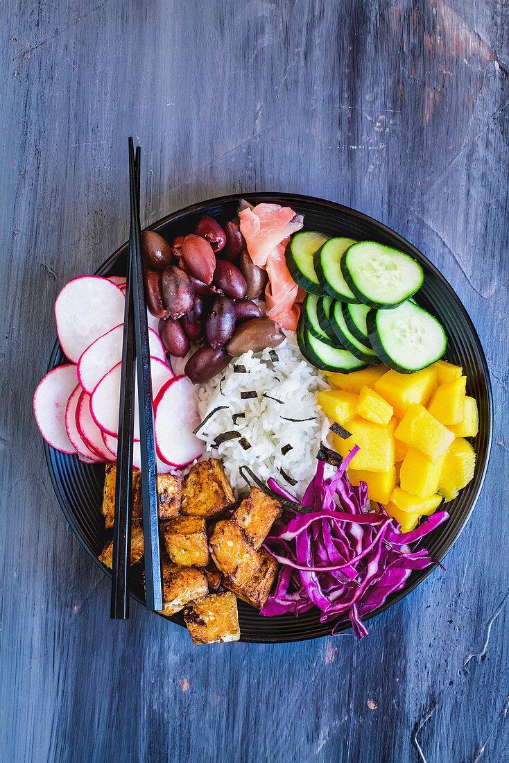 Buddha bowl with basmati rice, mango, fried tofu, purple cabbage, radishes, olives, pickled ginger and seaweed