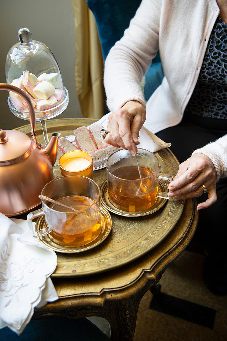 Teatime with a teapot, tea glasses and cake on a stylish side table