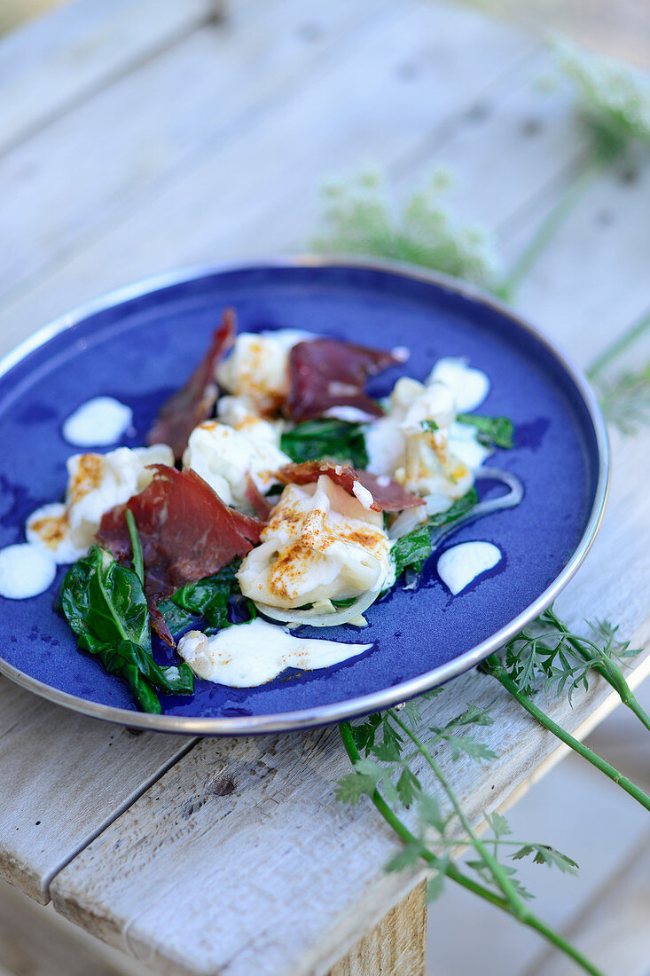 Turkish goat's cheese manti with pastirma and baby spinach