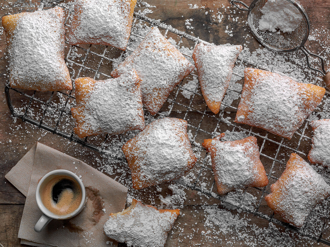 Beignets coated with powdered sugar and a cup of espresso