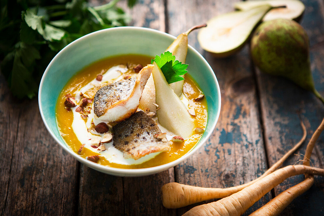 Carrot and parsnip curry soup with pear and trout