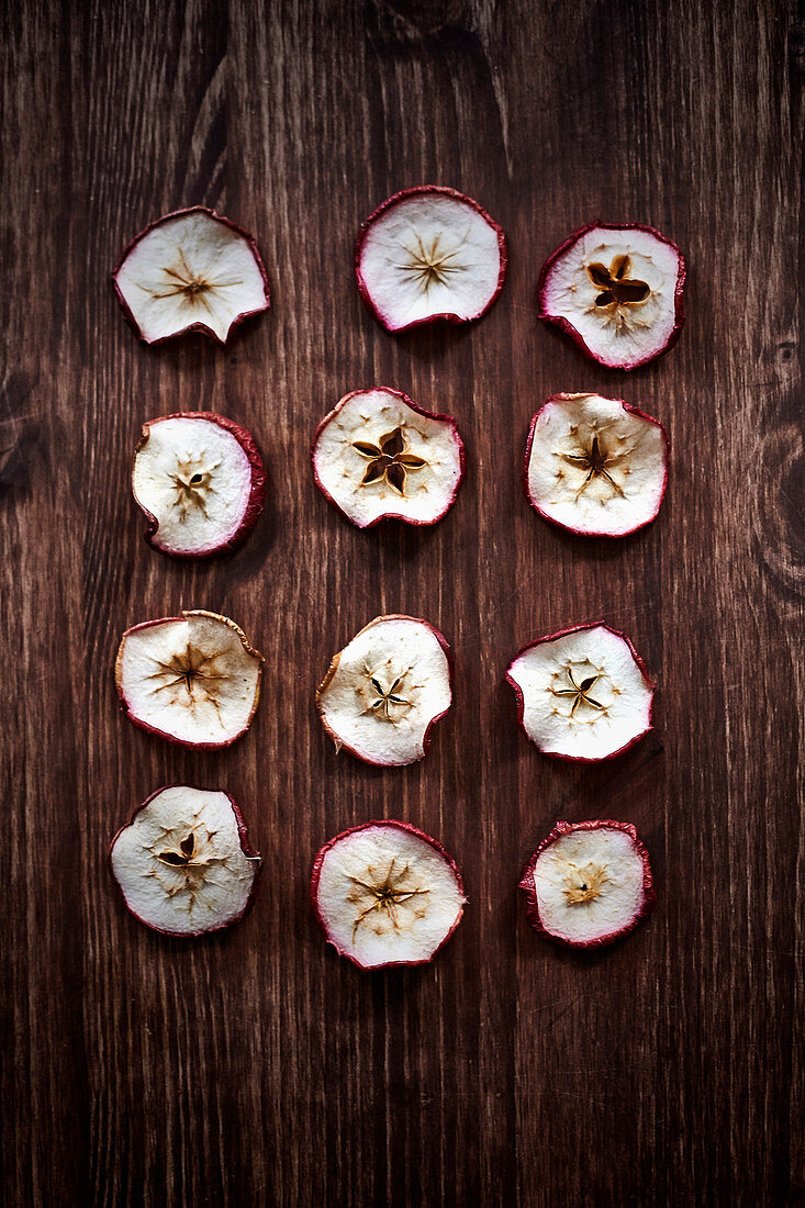 Dried apple slices on a wooden surface