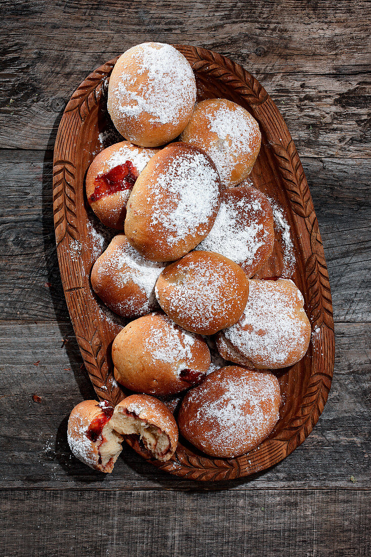 Buns with jam filling on a wooden plate
