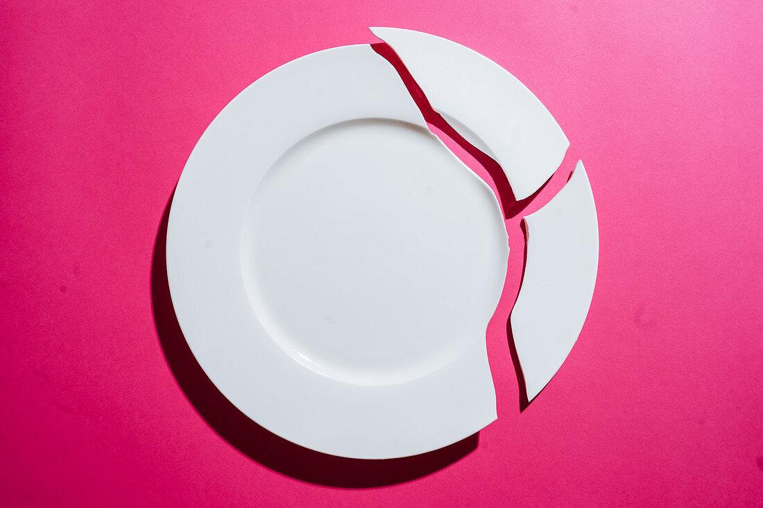 Zerbrochener weisser Teller auf rosa Hintergrund