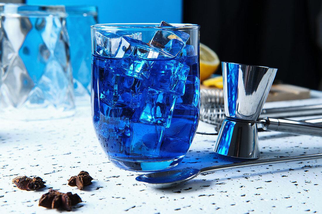Blauer Cocktail mit Eiswürfeln und Barutensilien auf Tisch