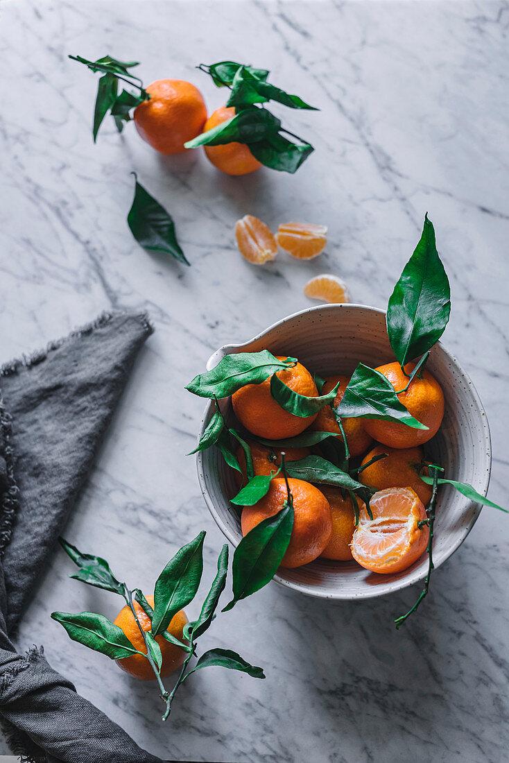 Orange tangerines in ceramic ornamental bowl on marble table