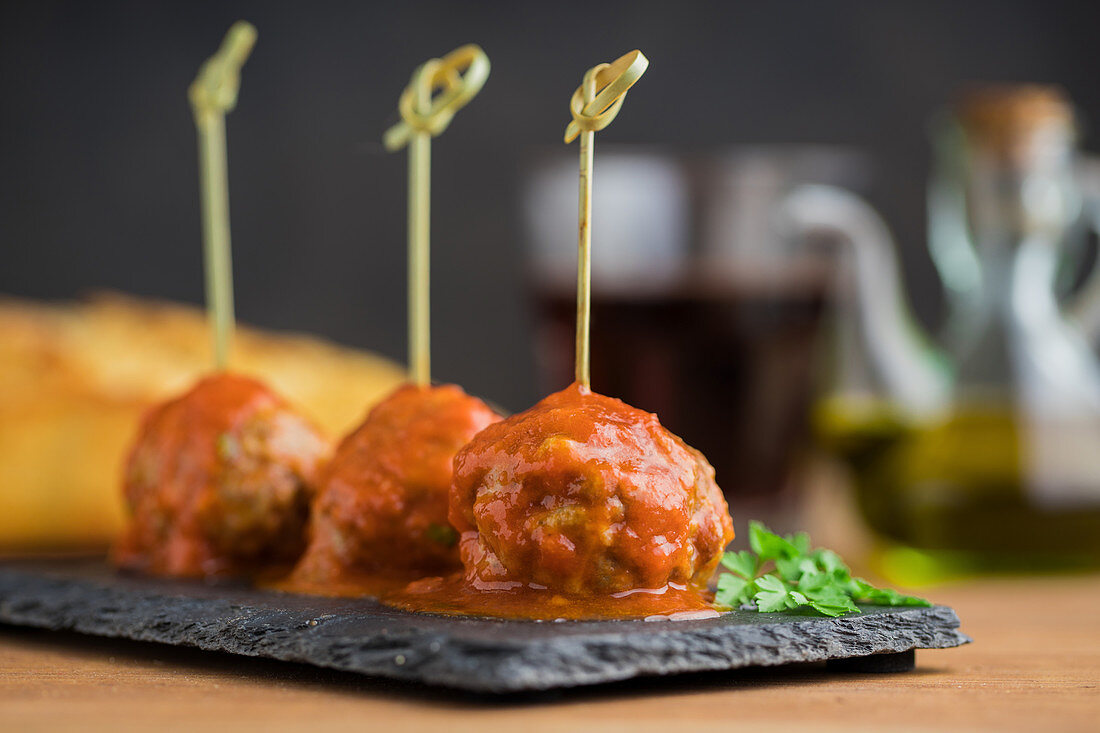 Meat balls with tomato sauce bonded with bamboo sticks on flat board on table