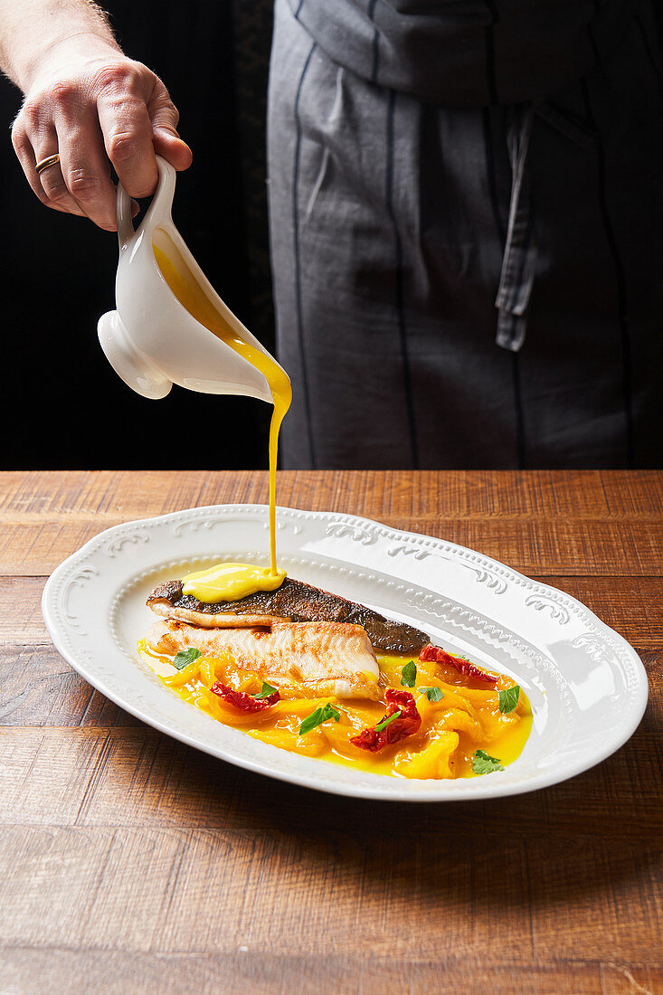 Chef using small cruet while pouring yellow thick sauce stewed red fish with colorful vegetables
