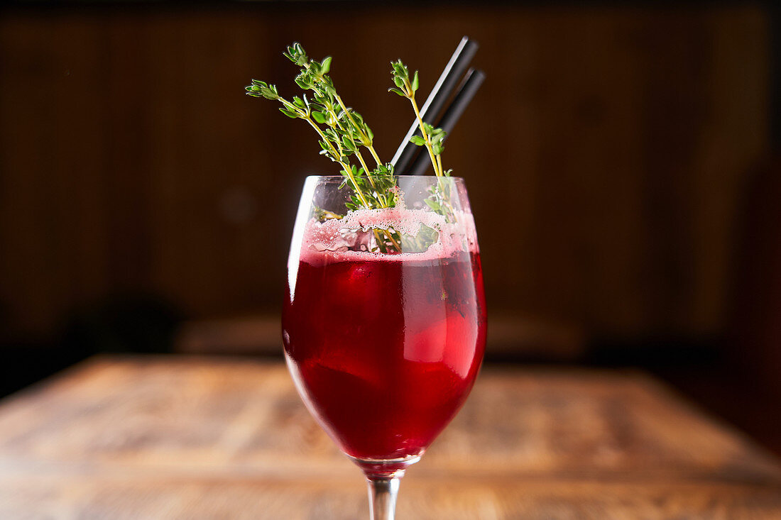 Red berry cocktail decorated with green rosemary in modern glass with tubes on wooden table in bar