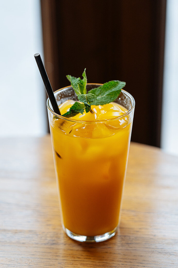 Yellow beverage in highball glass with ice decorated with fresh green mint on wooden table