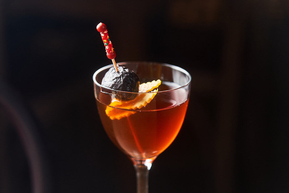 Red cocktail Manhattan garnished with cherry and orange zest on stick against dark background