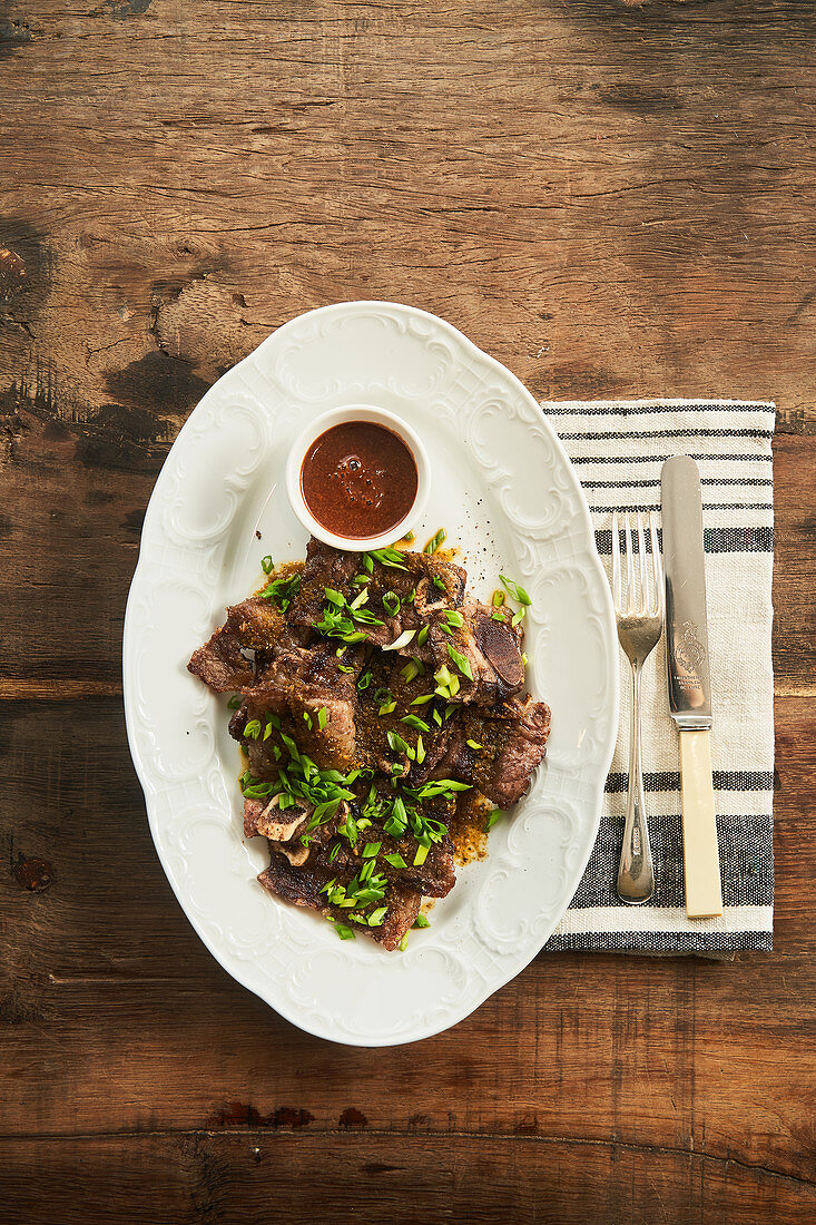 Baked meat with green onion and BBQ sauce on plate with cutlery on wooden rustic table
