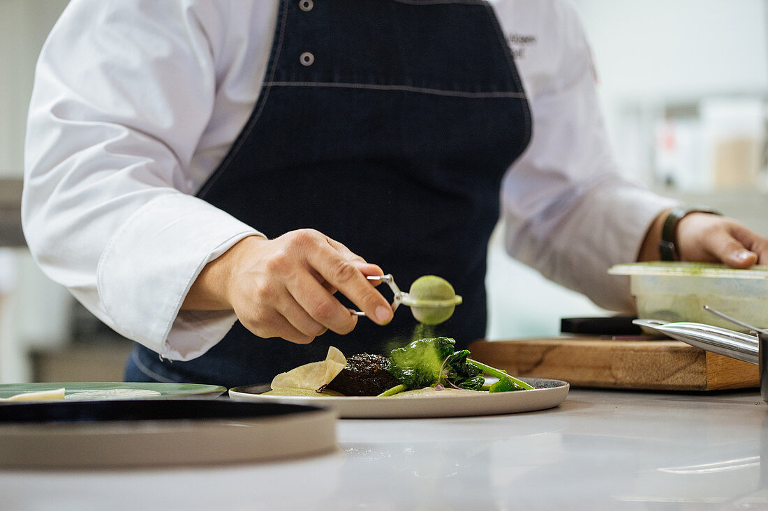 Chef preparing meat steak with green powder and herbs served on ceramic plate