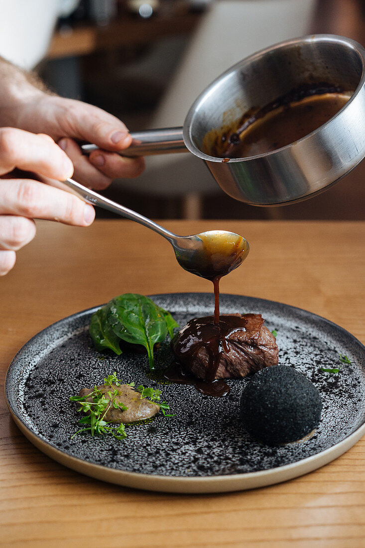 Chef pouring sauce on delicious gourmet meat steak with sauce and herbs served
