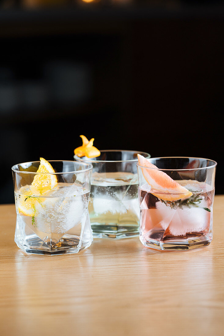 Glass cups with cold cocktails with various citruses placed on table against black background
