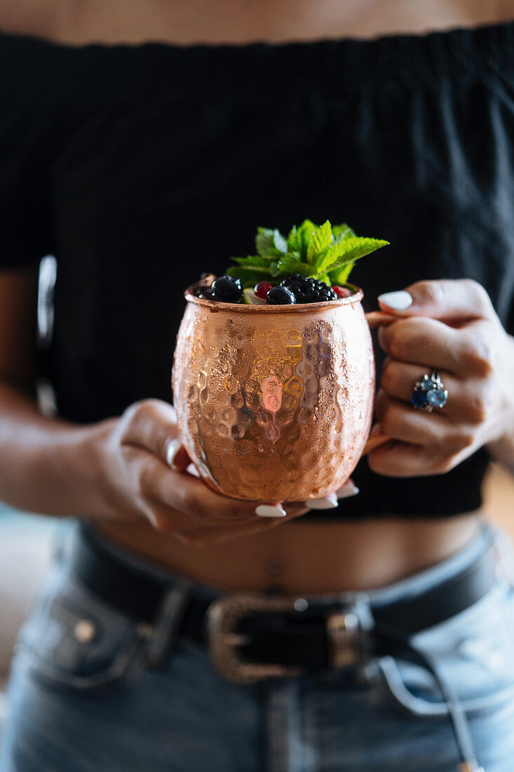 Female carrying metal mug of natural fruit drink with berries and mint leaves