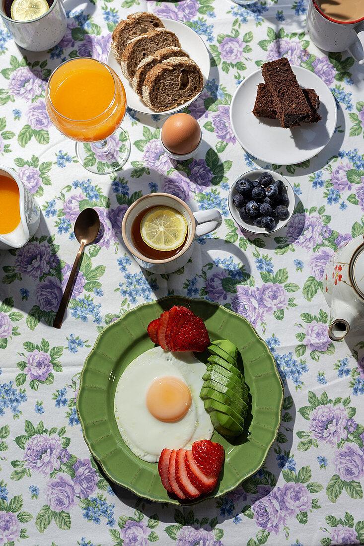 Üppiges Frühstück mit Eiern, Avocado, Obst, Kuchen, Toast, Tee und Orangensaft