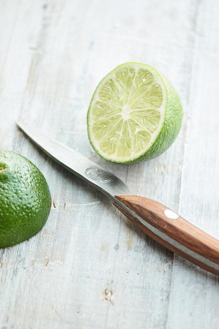 Halved lime with a kitchen knife on a light background