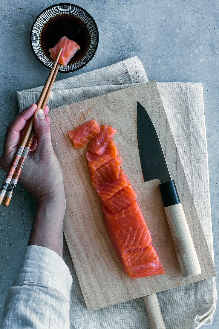 Person holding piece of salmon with chopsticks and dipping in sauce