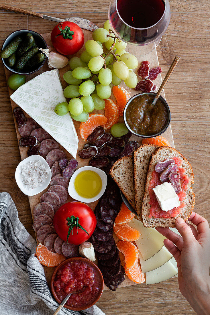 Persons eating snacks, sliced of meat, vegetables, fruits and glass of red wine