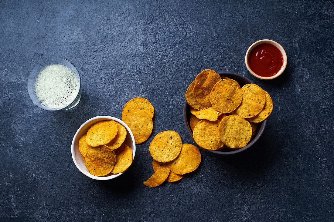 Mexican round-shaped nacho chips in bowls with hot chili salsa and a glass of beer