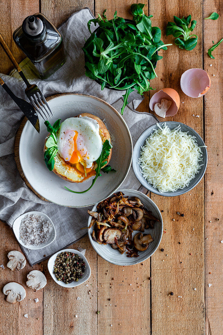 Fried egg on potato on wooden table with fried mushrooms, grated cheese and herbs