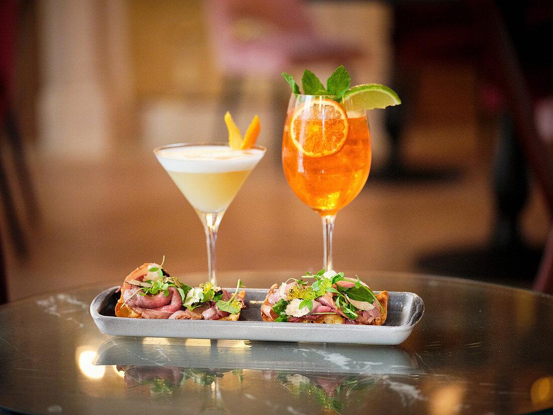 Yellow Cocktail with white foam, orange peel and orange cocktail with mint, lime and dish of roast beef