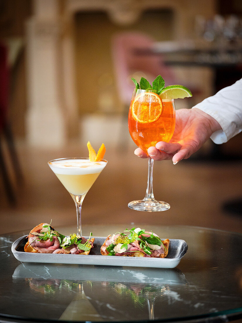 Hands holding yellow and orange cocktail decorated with mint and lime and a dish of roast beef