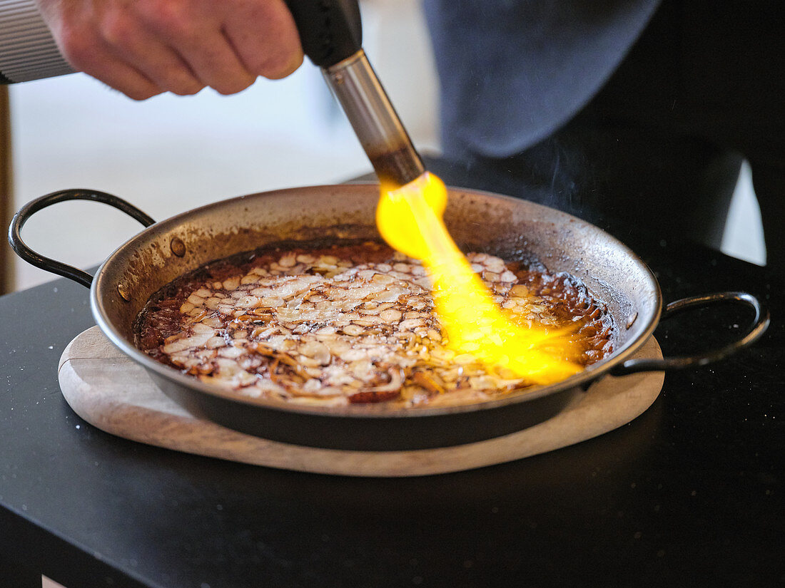 Chef using gas burner while cooking rice with octopus carpaccio and pepper aioli in metal pan