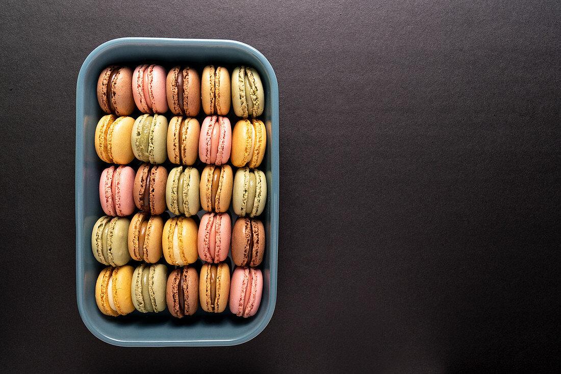 Verschiedenfarbige Macarons in blauem Behälter