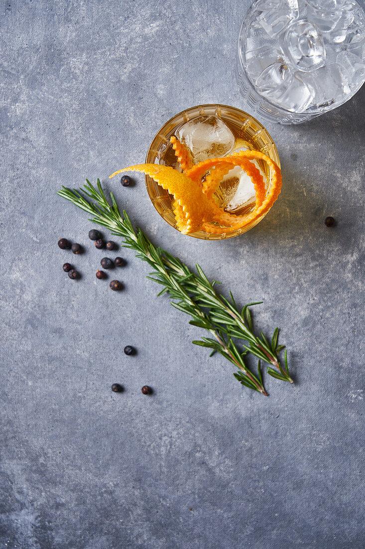 Whisky-Orange-Cocktail, daneben Rosmarinzweige und Pfefferkörner