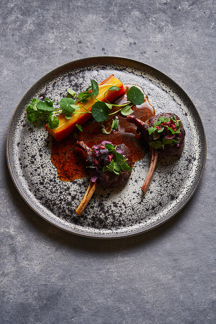 Meat medallions with herbs on plate on gray marble table