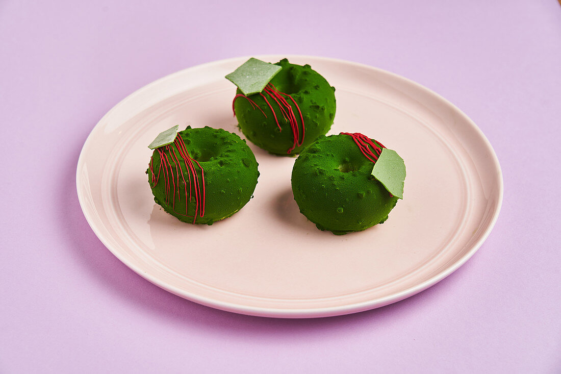 Doughnuts with green frosting placed on plate on lilac background
