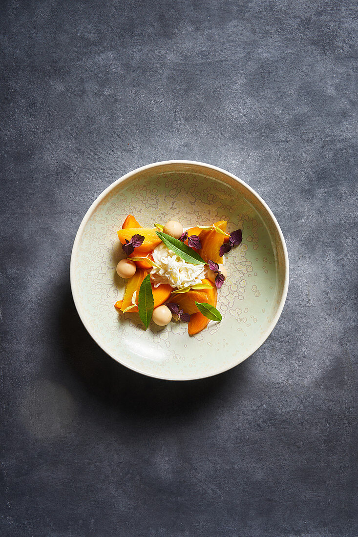 Mango salad with herbs placed on plate on gray tabletop
