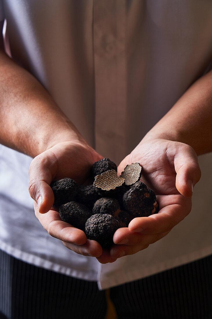 Cook demonstrating handful of black truffles