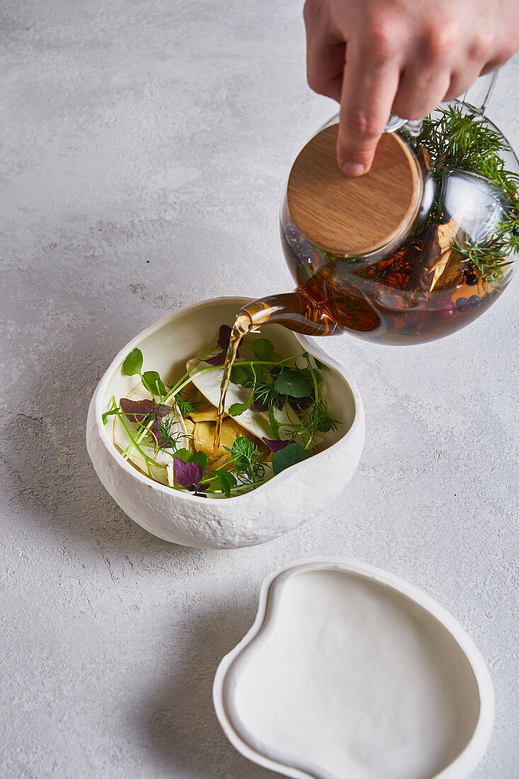 Person pouring fresh warm tea from glass teapot into ceramic bowl with herbs