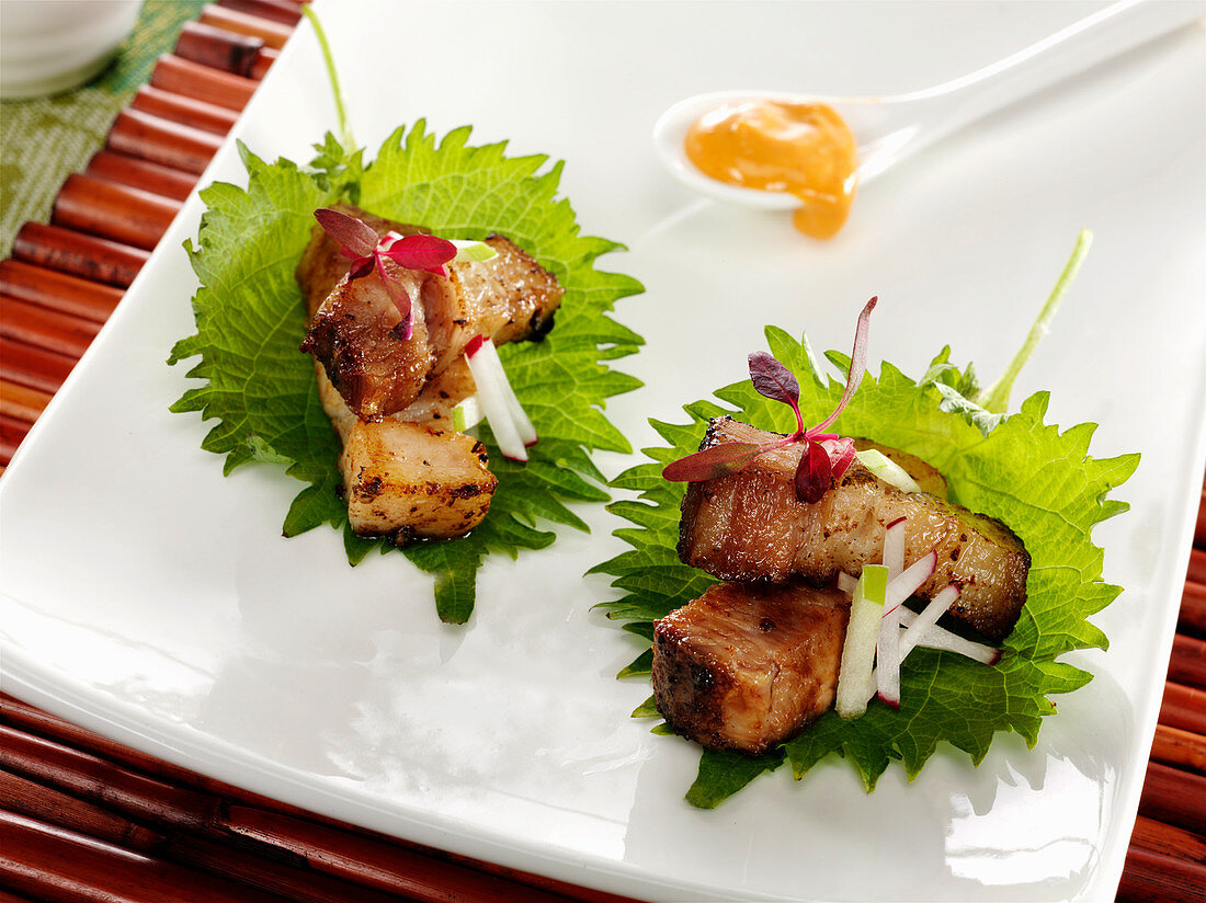 Roast pork belly with slivers of red radish and green apple served on shiso leaves with red amaranth microgreens