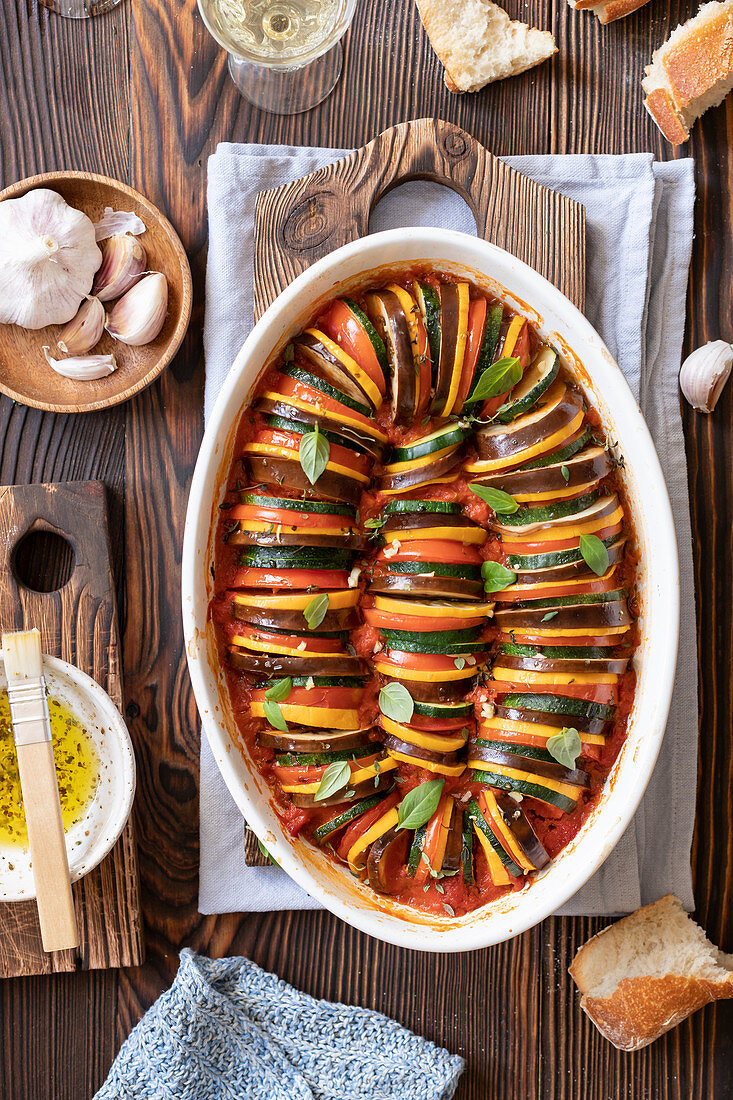 Ratatouille in a baking dish, bread, basil leaves, garlic, herb olive oil