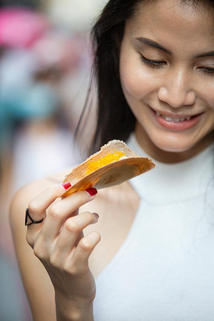 Junge Asiatin isst Kanom Buang (Crepe mit Cremefüllung und Foi Thong, Thailand)