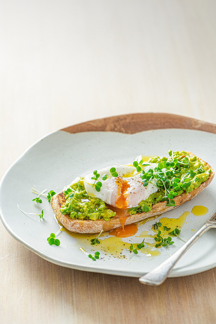 Poached egg on ciabatta toast with smashed avocado, cress and olive oil