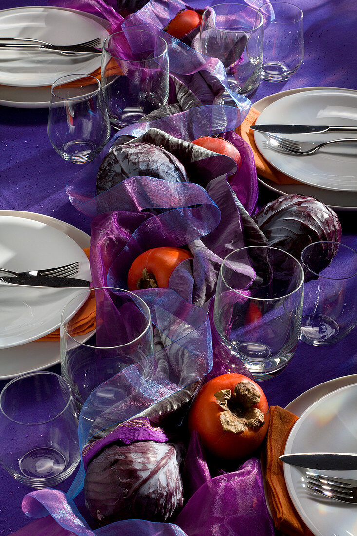Autumn table set in purple tones with red cabbage and persimmon
