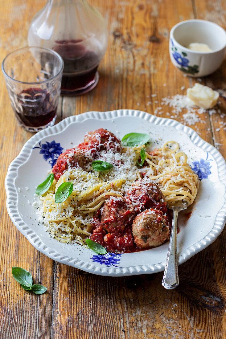 Spaghetti with tomato sauce and tuna meatballs, basil, parmesan, red wine