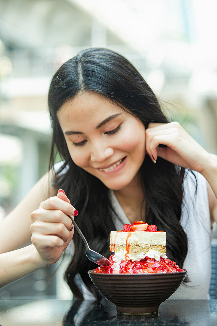 Young Asian woman eats a tiramisu strawberry ice cream sundae in a street cafe in Bangkok